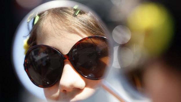Junge Frau blickt in den Rückspiegel einer Vespa