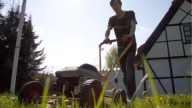 Jugendlicher mäht den Rasen.