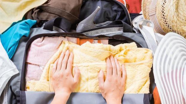 Jemand packt einen Koffer mit Sommerkleidern