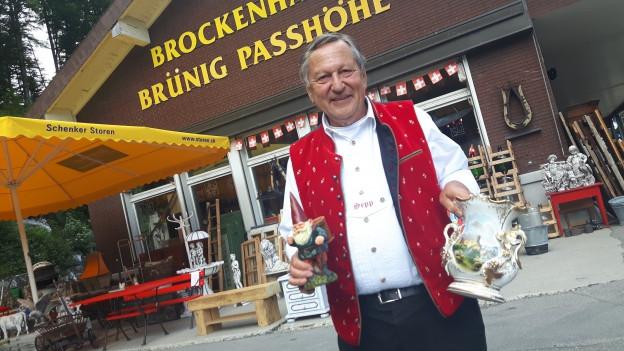 Im Vordergrund ein älterer kleiner Herr im leuchtendroten Gilet österreichischer Trachten und weissem Hemd, in den Händen hält er Porzellan-Gegenstände aus seinem Brockenhaus.