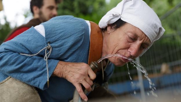 Pilgerin trinkt Wasser an einem Brunnen.