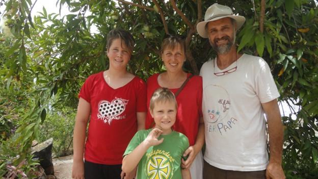 Familie Graf stehen unter einem exotischen Baum.