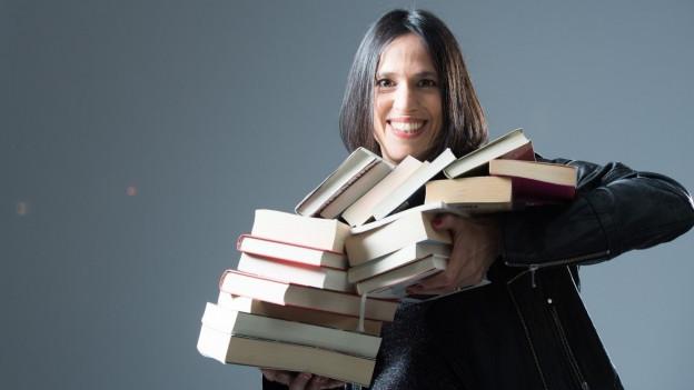 Annette König, SRF Literatur-Redaktorin mit einem Stapel Bücher