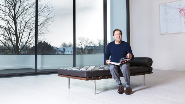 Georges Delnon sitzt auf einem Sofa in einem loftartigen Wohnzimmer. In der Hand hält er ein Buch.