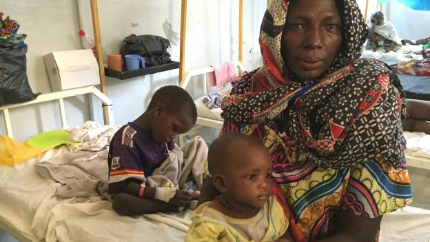 Eine junge Frau sitzt auf einer einfachen Spitalpritsche zusammen mit ihren zwei kleinen Kindern.