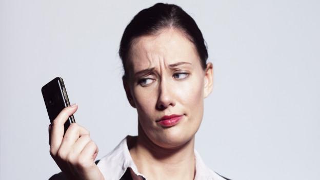 Frau blickt unzufrieden auf Handy.