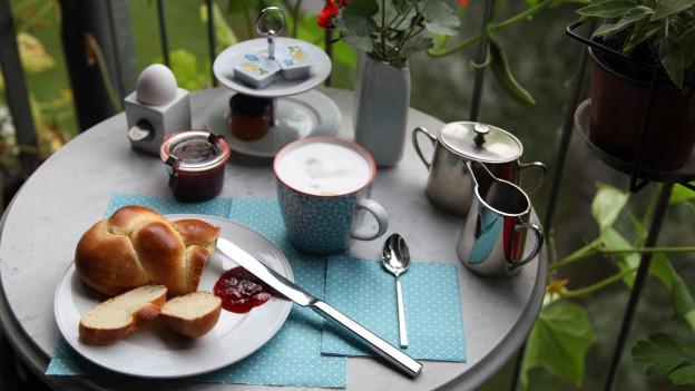 Auf einem Bistro-Tisch hat es ein feines Frühstück.