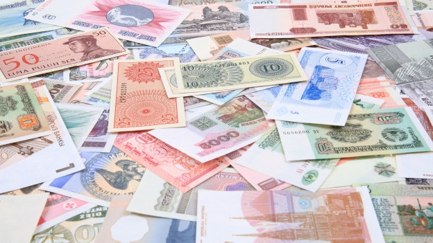 Blick auf einen Haufen Banknoten verschiedenster Währungen