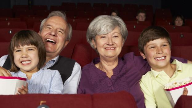 Grosseltern mit Enkeln im Kino.