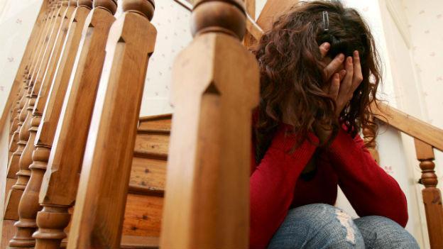 Eine verzweifelte Frau sitzt auf der Treppe.
