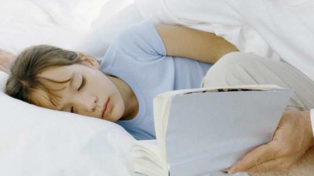 Ein Vater sitzt auf der Bettkante und liest seinem Sohn eine Geschichte vor.