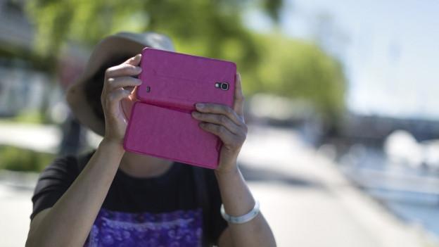 Eine Touristin hält ihr IPad vor das Gesicht und sucht.