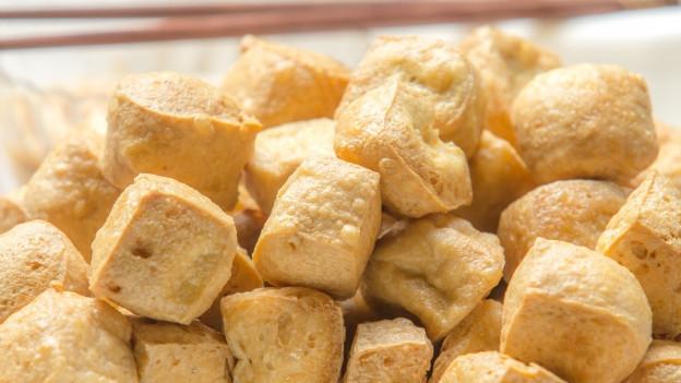 Ein Teller, darauf ganz viele gelbliche Tofu-Würfel aufgeschichtet.