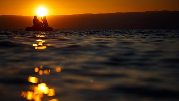 Ein Boot schaukelt im Licht des Sonnenuntergangs auf einem See.