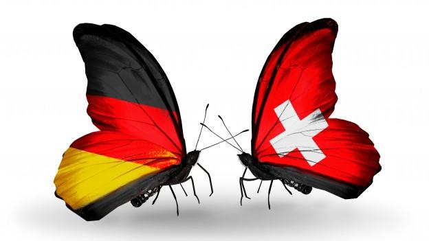 Zwei Schmetterlinge. Der eine hat die deutsche Flagge auf den Flügeln, der andere die Schweizer Flagge.