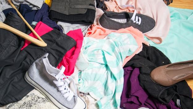 Turnschuhe, Pullis, verschiedene T-Shirts liegen wild durcheinander auf dem Boden.