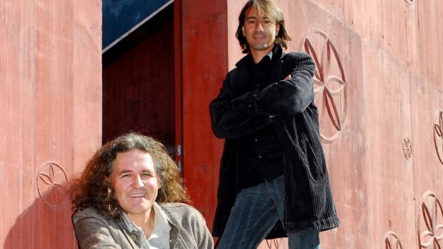 Linard Bardill sitzend, Pippo Pollina stehend auf einer Treppe.