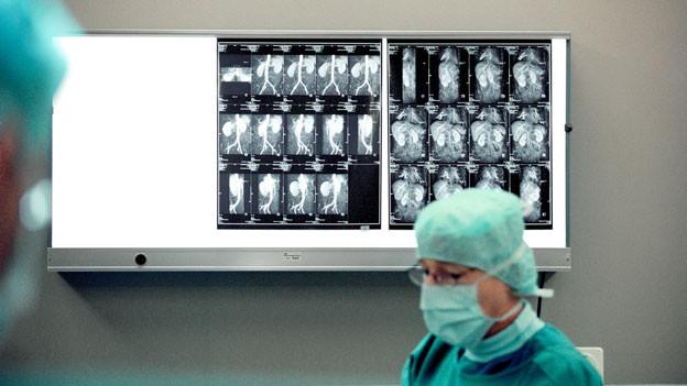 Ein Arzt steht vor Röntgenbildern.
