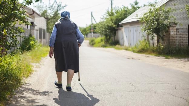 ältere Frau auf der Strasse läuft dem Horizont entgegen.