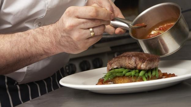 Ein Koch beträufelt ein Stück Fleisch mit Bratensauce.