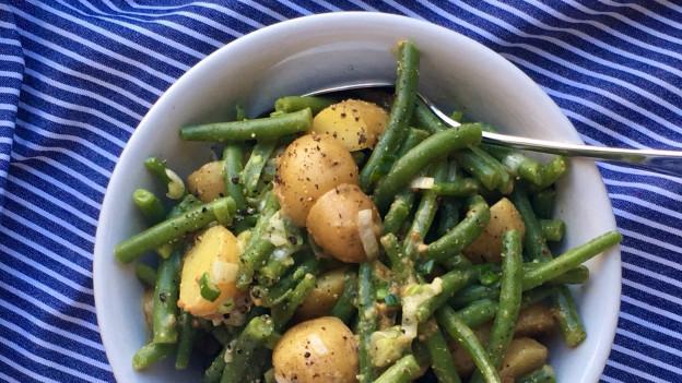 Schüssel mit Bohnen-Kartoffelsalat mit Frühlingszwiebeln und grobem Senf.