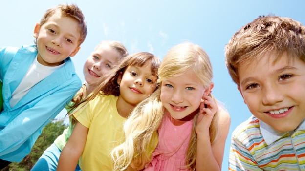 Portrait von Kindern, die in eine Kamera lachen vor einem blauen Himmel.