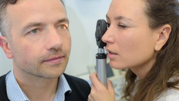 Augenärztin schaut Patienten ins Auge.