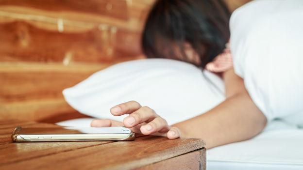 Frau greift im Bett zum Smartphone.