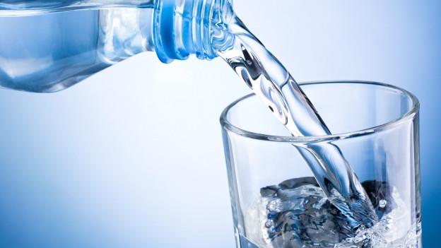 Wasser wird in ein Glas eingeschenkt.