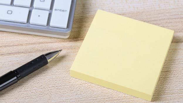 Nahaufnahme einer Tastatur, eines Post it - Blocks und eines Kugelschreibers.