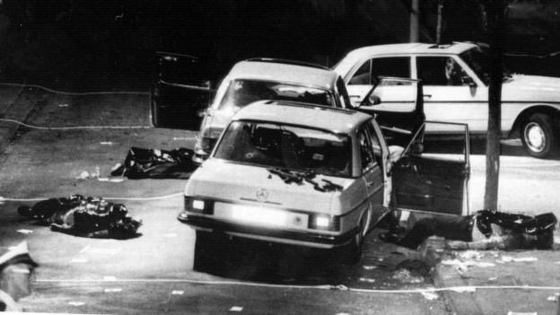 Schwarzweissbild von einem Terrorakt in Deutschland. Zwei kaputte Autos.