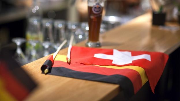 Deutsche und Schweizer Fahne auf einem Bardtresen.