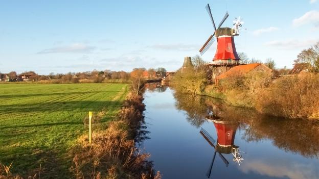 Ostfriesische Landschaft mit Fluss und Windmühle