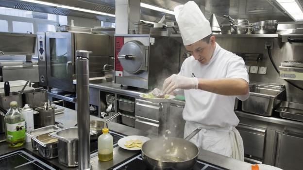 Ein Koch streut Gemüse in eine heisse Pfanne.