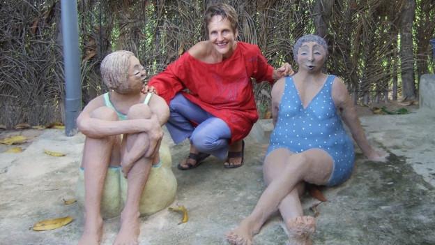 Regula Trutmann kniet zwischen ihren lebensgrossen Frauenskulpturen