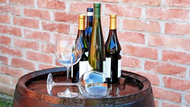 Weinflaschen und Weingläser auf einem Holzfass