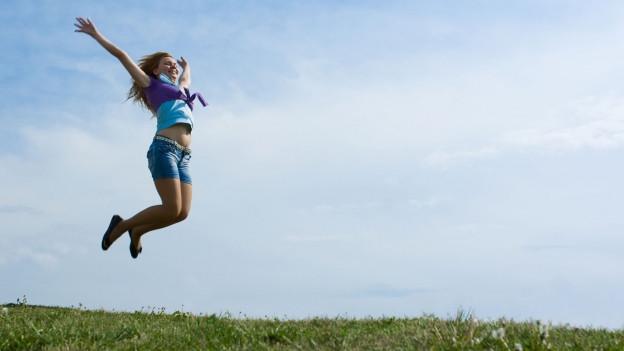 Junge Frau springt auf einer Wiese in die Luft