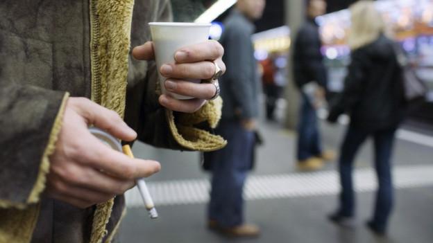 Mann steht mit Zigarette auf Bahnperron.
