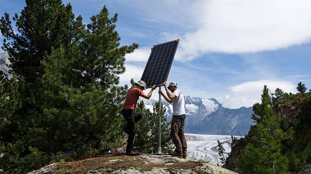 Zwei Männer bringen oberhalb eines Gletschers ein Solarpanel an.