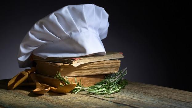 Ein Stapel Kochbücher mit einer Kochmütze darauf.