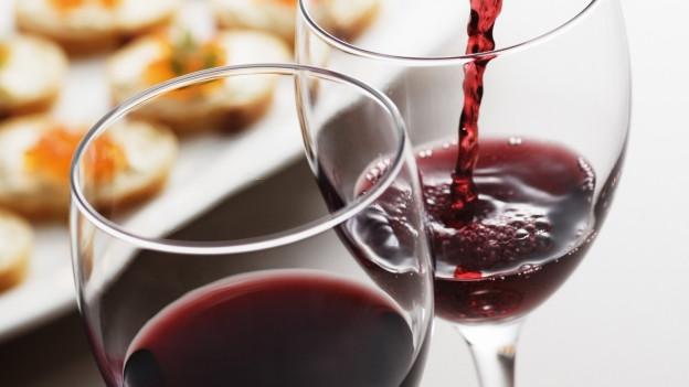 Zwei Gläser Wein, wobei bei einem gerade eingeschenkt wird.