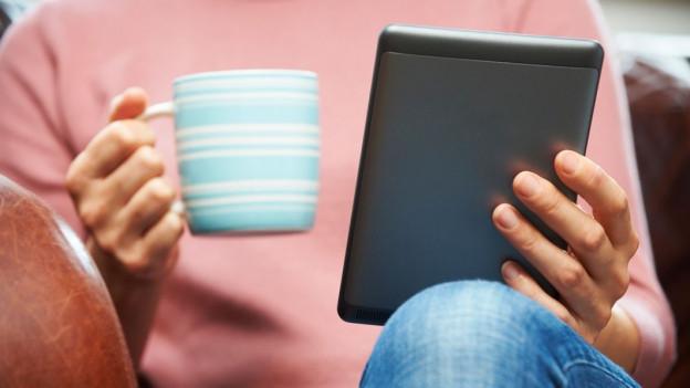 Eine Person hält eine Tasse und den E-Reader in der Hand.