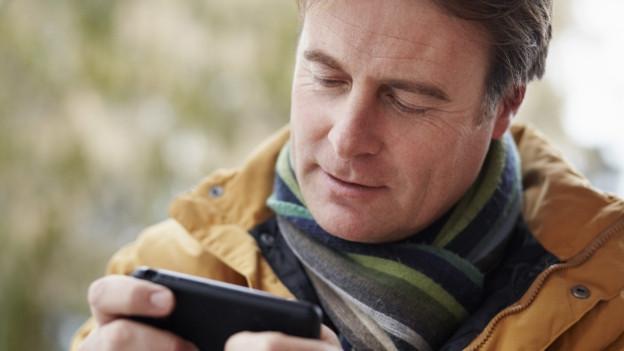 Mann mit Smartphone im Schnee.