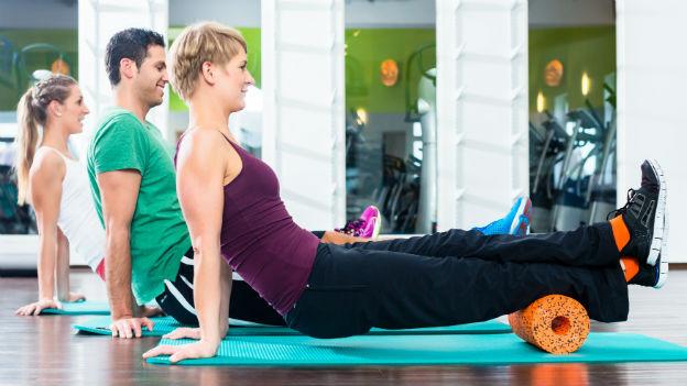 Frau benutzt im Fitnesscenter eine Massagerolle.