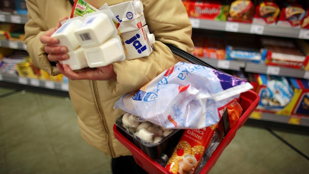 Eine Person trägt einen vollen Einkaufskorb und Esswaren in den Händen.