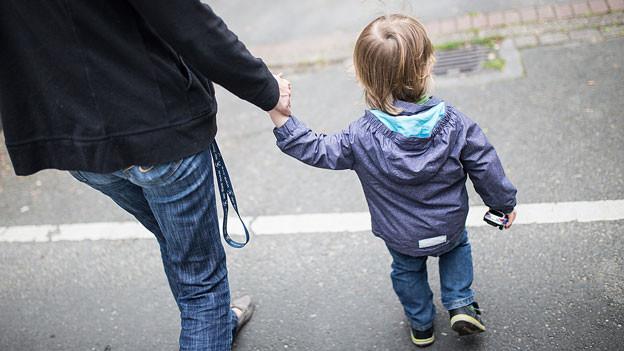 Eine Mutter hält ein Kind an der Hand.