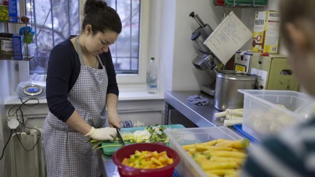 Eine junge Frau schnetzelt in einer Küche Gemüse.