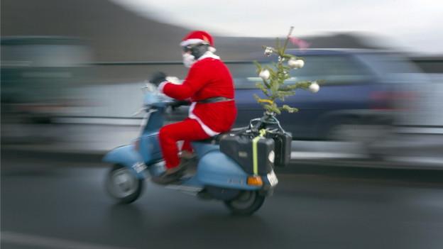 Weihnachtsmann fährt mit einer Vespa davon.