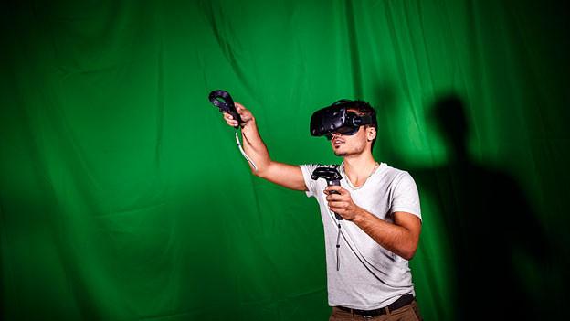 Ein Mann mit VR-Brille vor grünem Hintergrund.