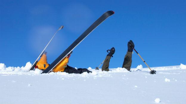 Skifahrer liegt nach Sturz im Schnee.